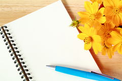 Close up open blank spiral note book and yellow flower on wood background. Open blank spiral note book and yellow flower on wood background Royalty Free Stock Photo