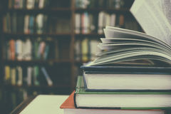Close up of open book and Stack of books on desk with vintage filter blur background Stock Photo