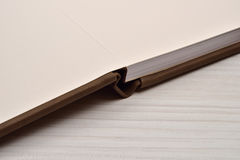 Close up of open brown leather photo album on white wooden backg Stock Photo