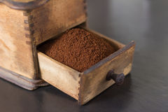 Close up of open drawer of coffee grinder. Close up view of fine coffee grounds in open drawer of old wooden manual grinder on table Royalty Free Stock Images