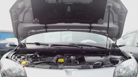 Open hood, car engine compartment. Close-up of an open hood, engine compartment of a gray car stock footage