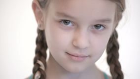 Close-up open look of Caucasian girl with pigtails opening and closing eyes. Neutral emotion look into the camera.  stock video