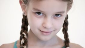 Close-up open look of a Caucasian girl with a pigtails opening and closing her eyes. Angry and blind in the camera.  stock video footage