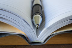 Close-up of open notebook and pen Stock Photo