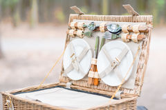Close up of an open picnic basket over wooden table in the park. Stock Photos