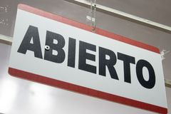 Close-up of an open sign in spanish. `Abierto`. An spanish open sign hanging in a store. Abierto meaning open stock photos