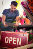 Close-Up of open signboard while of male florist using digital tablet in background. At his flower shop Stock Images
