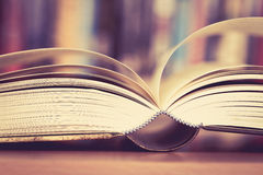 Close up opened book page with blurry bookshelf background for e Royalty Free Stock Photos