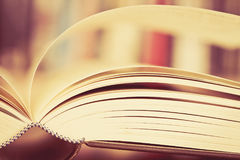 Close up opened book page with blurry bookshelf background for e Royalty Free Stock Image