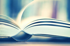 Close up opened book page with blurry bookshelf background for e Royalty Free Stock Images