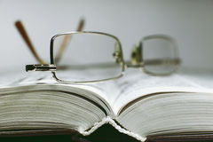 Close up opened book page and reading eyeglasses Stock Photos