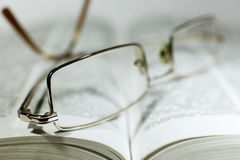 Close up opened book page and reading eyeglasses Royalty Free Stock Image