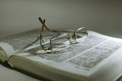 Close up opened book page and reading eyeglasses stock photography