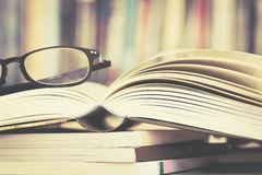 Close up opened book page and  reading eyeglasses with  blurry b Stock Images