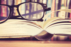 Close up opened book page and  reading eyeglasses with  blurry b Royalty Free Stock Images