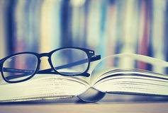 Close up opened book page and  reading eyeglasses with  blurry b Stock Photos