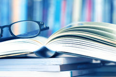 Close up opened book page and reading eyeglasses with blurry boo. Kshelf background for education and publication concept , extremely shallow DOF Royalty Free Stock Image