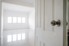 Close-up opened door with empty white room space, and bright light from window Royalty Free Stock Photos