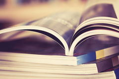 Close up opened magazine page with  blurry bookshelf background Stock Image