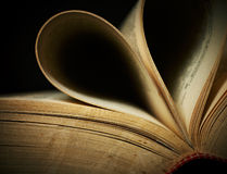 Close-up of opened old book. Close-up of opened old book against black background. Shallow DOF Royalty Free Stock Images