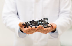 Close up of optician with glasses at optics store Stock Photos