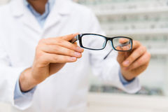 Close up of optician with glasses at optics store Royalty Free Stock Photography
