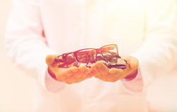 Close up of optician with glasses at optics store Royalty Free Stock Photos