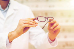 Close up of optician with glasses at optics store Stock Image