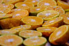 In selective focus a pile of fresh oranges cut in a half stock photography