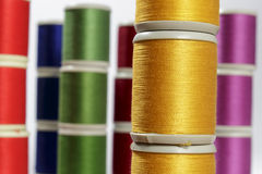 Close-up orange cotton thread bobbins. Other color threads in background Royalty Free Stock Photos