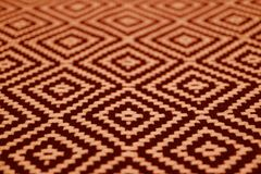 Close-up of orange and dark brown colored ethnic pattern fabric. Texture background abstract art backdrop banner blurred cloth craft decor decoration royalty free stock images