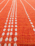Close up of orange fabric patterns with white lines. Closeup of orange fabric with white dashed lines converging Stock Image