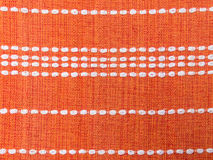 Close up of orange fabric patterns with white lines. Close up of orange fabric pattern details with white dashed lines parallel Stock Image
