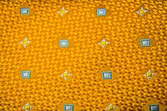 Orange fabric texture. A close up of a Orange fabric with white and yellow square stitching Stock Photography