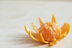 Close-up orange mandarin or tangerine with peeled peel similar as flower or sun on white background. Close-up fresh orange mandarin or tangerine with peeled royalty free stock photo