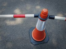 Close-up Orange Traffic Cone with Tubular Bars as Fence. High Angle View of Orange Traffic Cone with Tubular Bars as Fence stock photo