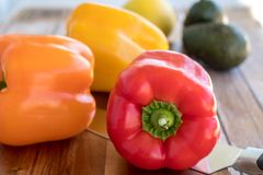 Close up of orange, yellow and red bell peppers and lemon. Close up of Cutting board with yellow pepper, red pepper, orange bell pepper, avocados and lemon and Stock Photos