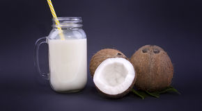 Close-up of organic brown coconuts and a mason jar with natural coconut milk and a yellow straw on a dark blue Stock Photography