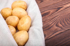 Close-up of organic new potatoes on a light grey fabric and on a dark brown wooden table. Fresh, organic, raw potatoes. Vegetables Stock Photo