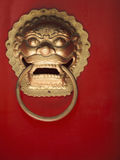 Close-up of ornate gold door knocker on red door Stock Photography