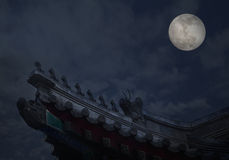 Close-up of ornate roof tiles on Chinese building with moon background, night. Stock Image