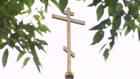 Close-up of an Orthodox cross on a church through green leaves against a white sky. stock video