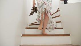 Close-up Os pés desencapados fêmeas descem as escadas de madeira uma mulher em uma saia longa bonita anda abaixo das escadas pree filme