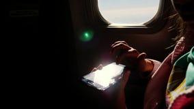 Close-up os raios do sol são refletidos no telefone silhueta escura das mãos e do telefone celular da criança contra o avião video estoque