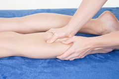 close up of osteopath applying pressure with thumb on female calf muscle stock photography