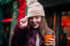 Close up outdoor fashion portrait of stylish young woman having fun, emotional face , laughing, looking down. Urban city street st. Outdoor fashion portrait of Royalty Free Stock Photo
