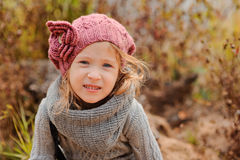 Close up outdoor portrait of adorable smiling child girl in pink knitted hat and grey sweater Stock Photo
