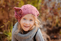 Close up outdoor portrait of adorable smiling child girl in pink knitted hat and grey sweater Royalty Free Stock Image