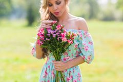 Close-up outdoor portrait of a beautiful blonde woman. attractive happy girl in a field with bouquet of flowers. Outdoor portrait of a beautiful blonde woman royalty free stock photography