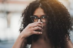 Portrait of curly girl in glasses drinking coffee outdoors royalty free stock image